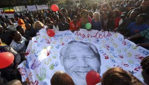 Well-wishers hold a giant banner with an image of Mandela outside the Medi-Clinic Heart Hospital in Pretoria